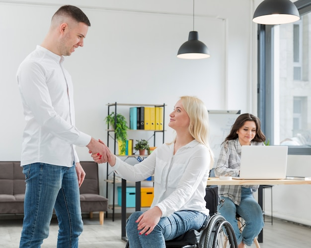 Mulher em cadeira de rodas, apertando a mão com colega de trabalho