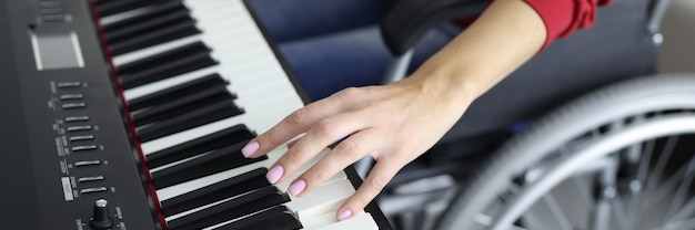 Mulher em cadeira de rodas apertando as teclas do piano, close-up