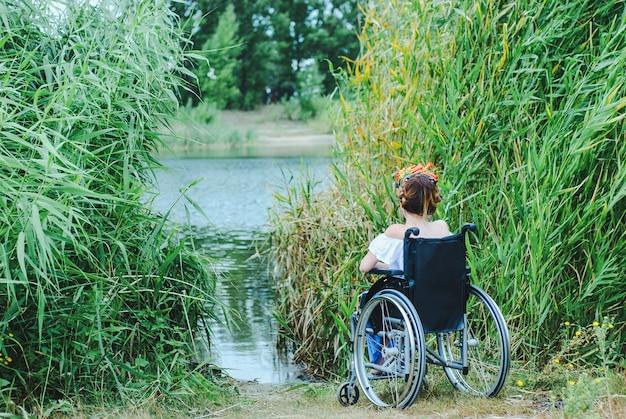 Mulher em cadeira de rodas, aproveitando o tempo olhando para o lago