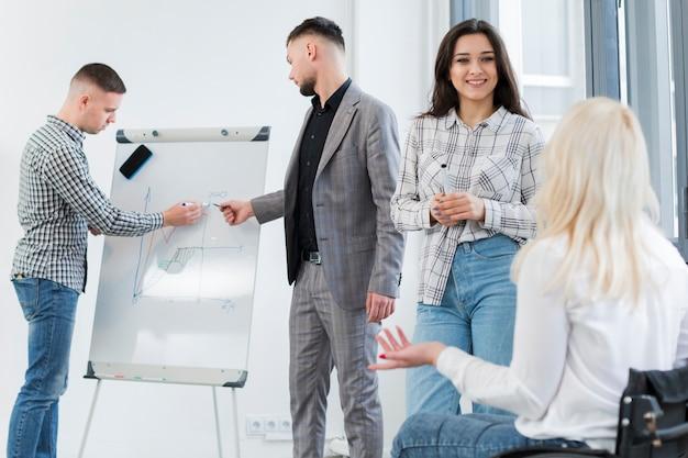 Mulher em cadeira de rodas, conversando com o colega no trabalho