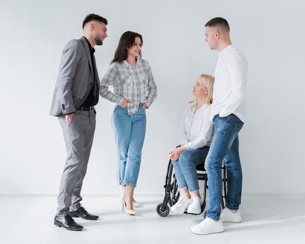 Mulher em cadeira de rodas, conversando com seus colegas de trabalho