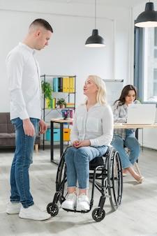 Mulher em cadeira de rodas, conversando com um colega de trabalho