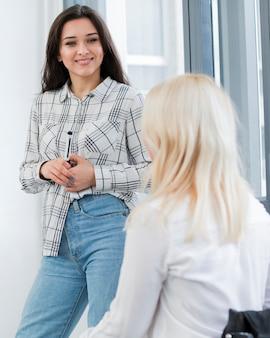 Mulher em cadeira de rodas, conversando com uma colega no trabalho