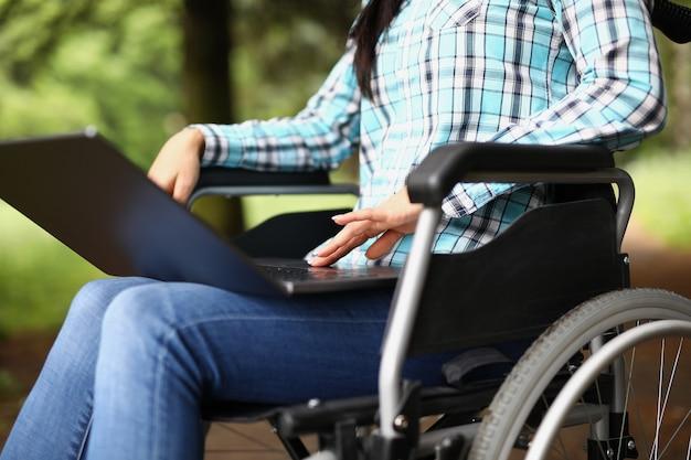Mulher em cadeira de rodas de joelhos com laptop