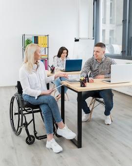 Mulher em cadeira de rodas, discutindo com o colega de trabalho na mesa