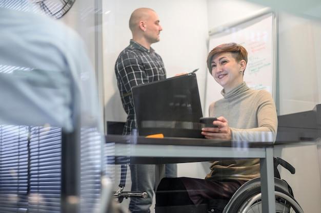Mulher em cadeira de rodas e colegas de trabalho