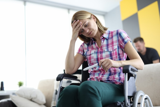 Mulher em cadeira de rodas está sentada e olhando para o teste de gravidez