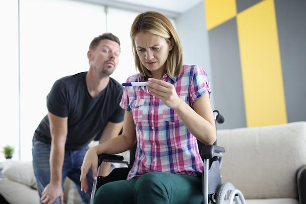 Mulher em cadeira de rodas observa atentamente o teste de gravidez por trás do homem espiando