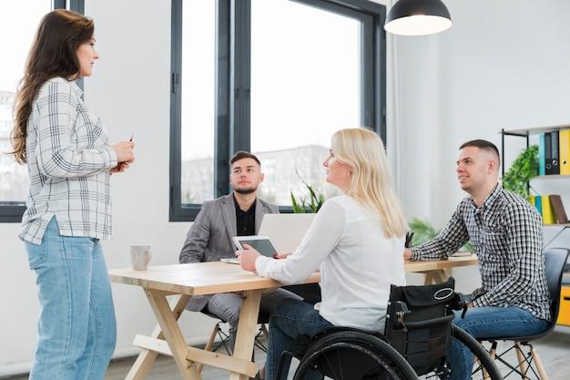 Mulher em cadeira de rodas, participando de reunião no escritório