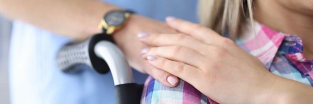 Mulher em cadeira de rodas, segurando a mão de um médico.