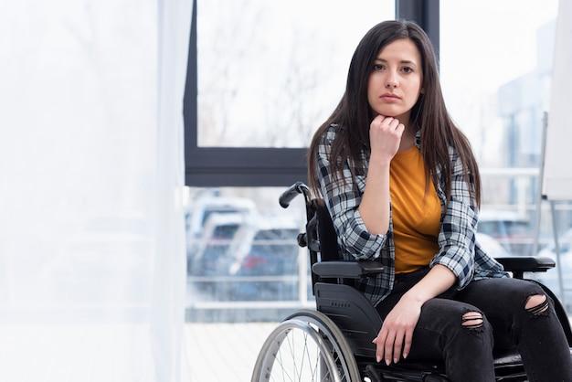 Mulher em cadeira de rodas sendo triste