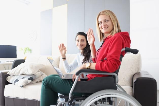 Mulher em cadeira de rodas sentada com um laptop e acenando com a mão