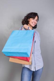 Mulher, em, calças brim, com, bolsas para compras
