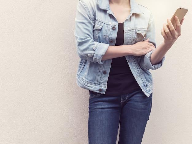 Mulher, em, calças brim, moda, segurando, telefone móvel