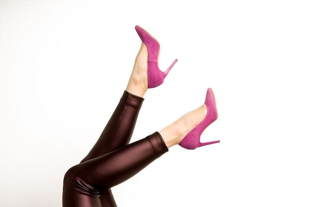 Mulher em calças de couro e sapatos de salto alto rosa em um fundo branco.
