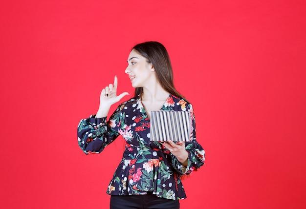Mulher em camisa floral segurando uma caixa de presente prata e parece pensativa.
