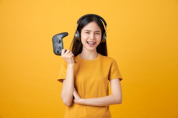 Mulher em camiseta amarela casual e jogando videogame usando joysticks com fones de ouvido.