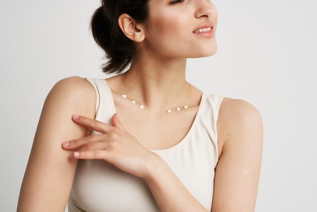 Mulher em camiseta branca creme corporal rejuvenescimento da saúde