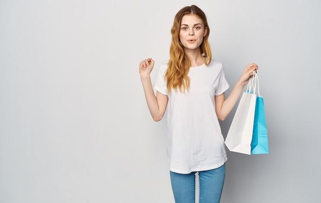 Mulher em camiseta branca e calça jeans nas mãos