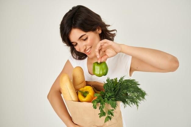 Mulher em camiseta branca entrega de comida saudável em supermercado de mercearia