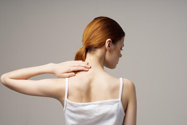 Mulher em camiseta branca reumatismo dor no pescoço problemas de saúde isolados fundo
