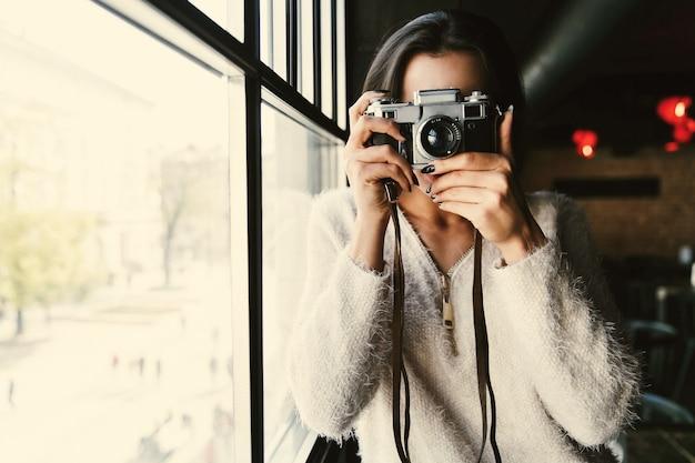 Mulher em camisola branca fica com câmera antes de uma janela brilhante