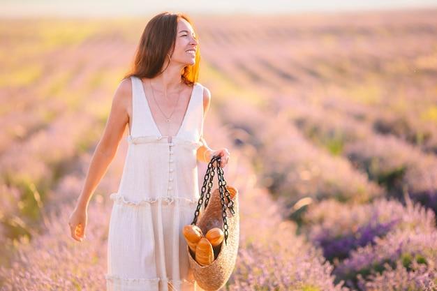 Mulher em campo de flores de lavanda com vestido branco e chapéu