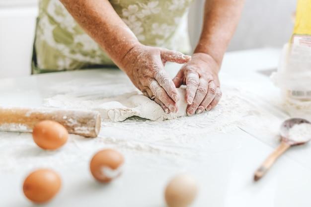 Mulher em casa amassando massa para cozinhar pão ou pizza. conceito de comida caseira. estilo de vida