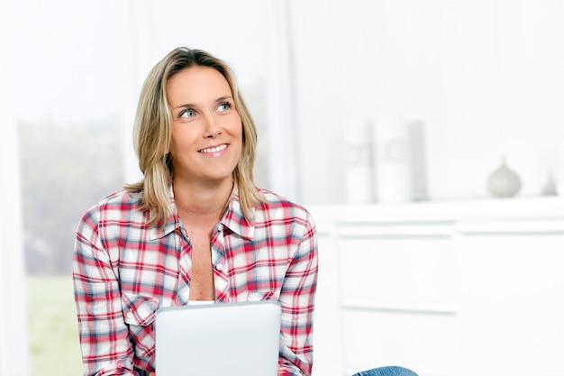 Mulher em casa com tablet olhando para alguém