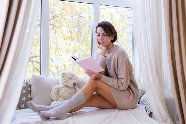 Mulher em casa com um notebook sentada no parapeito da janela, com um suéter confortável e meias quentes de lã, o frio fora da janela
