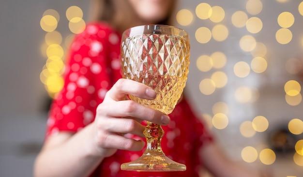 Mulher em casa decorada para o natal, segurando um copo de vinho e um brinde, close-up.