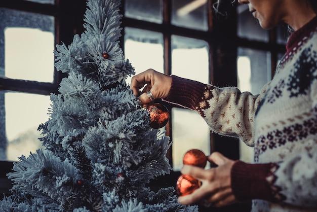 Mulher em casa decorando árvore de natal