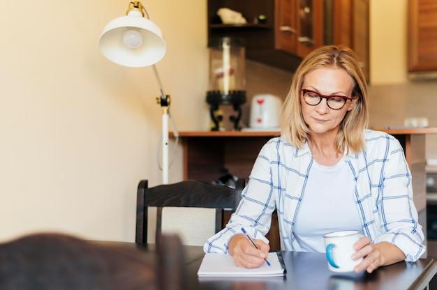 Mulher em casa durante a quarentena, escrevendo e tomando café