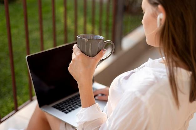 Mulher em casa em quarentena, trabalhando com laptop e bebendo café