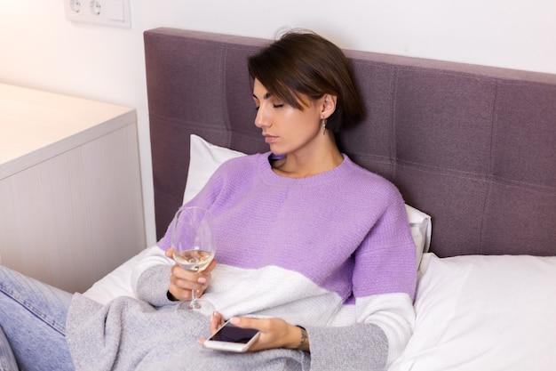 Mulher em casa entediada e cansada adormeceu com um copo de vinho e o telefone na mão
