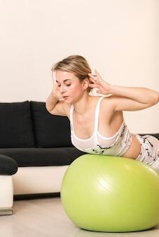 Mulher em casa exercitando na bola de fitness