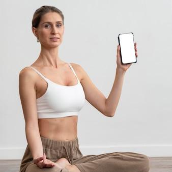 Mulher em casa fazendo ioga e segurando um smartphone