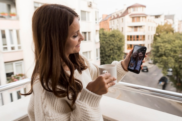 Mulher em casa fazendo videochamadas com amigos em quarentena com café