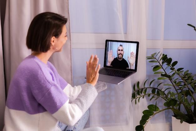 Mulher em casa fazendo videochamadas com os amigos, marido e namorado, conversando on-line em um laptop