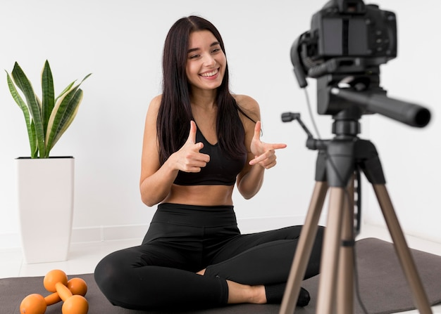Mulher em casa fazendo vlogs com a câmera enquanto se exercita
