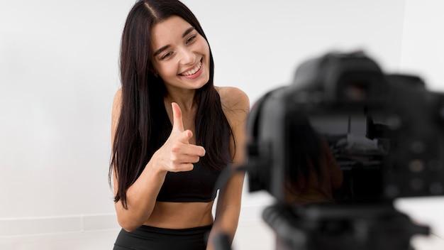 Mulher em casa fazendo vlogs com a câmera