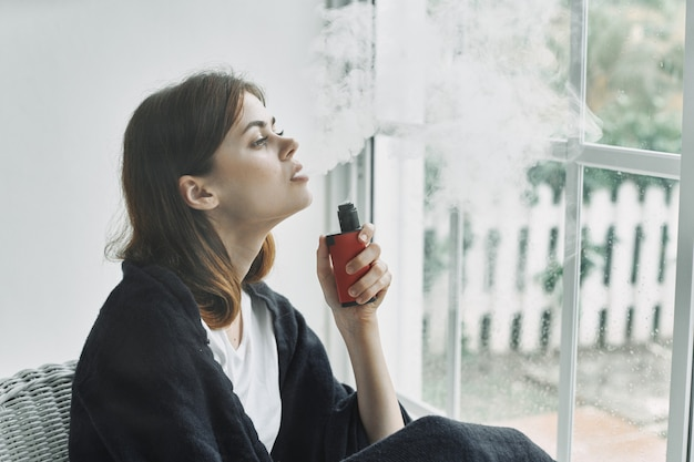 Mulher em casa perto da janela fuma vapor, estilo de vida de férias