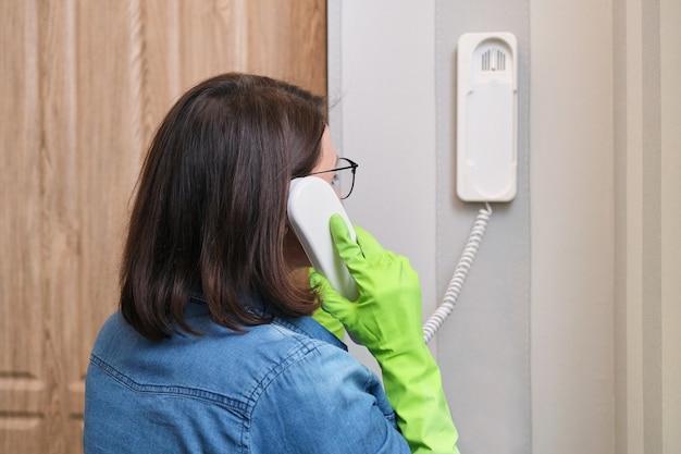 Mulher em casa perto da porta da frente falando no interfone, atendendo a chamada, segurando o telefone do segurança na mão