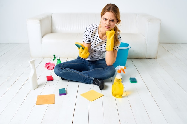 Mulher em casa perto do sofá lavando o chão