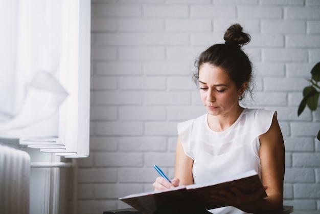 Mulher em casa que guarda o negócio de trabalho do caderno de casa.