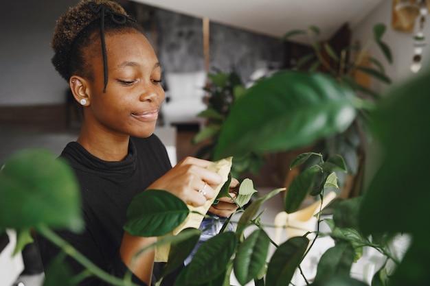 Mulher em casa. rapariga com uma camisola preta. mulher africana usa o pano. pessoa com vaso de flores.