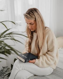 Mulher em casa rezando com a bíblia