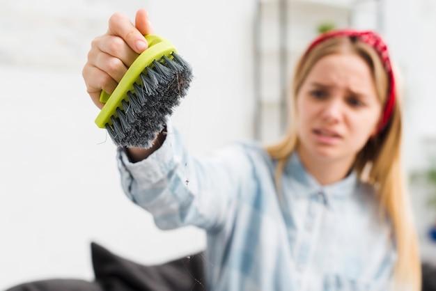 Mulher em casa segurando a escova