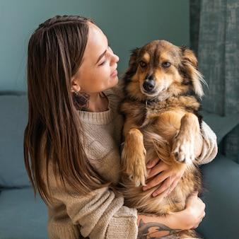 Mulher em casa segurando seu cachorro fofo durante a pandemia