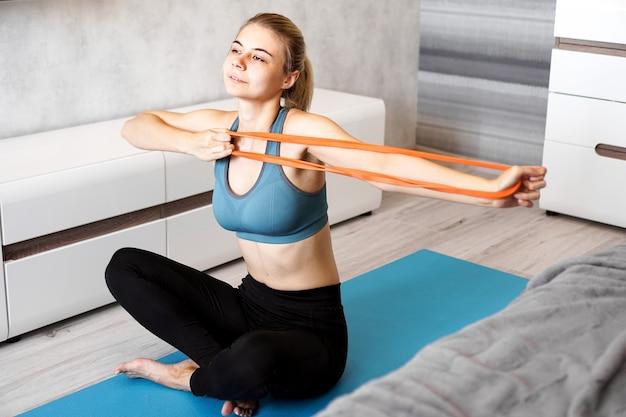 Mulher em casa tentando perder peso e tem treino com elástico nas mãos.